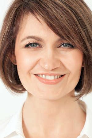 Attraktive lächelnde erwachsene Frau Blick auf Kamera in Nahaufnahme.