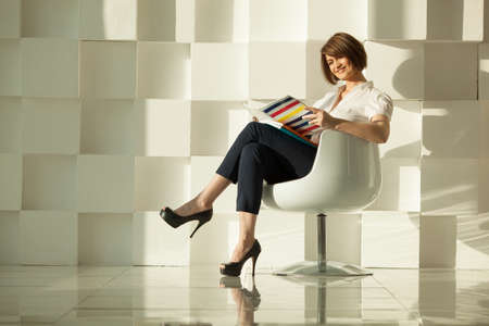 Elegant businesswoman reading magazine while sitting in chair against of white modern wall.