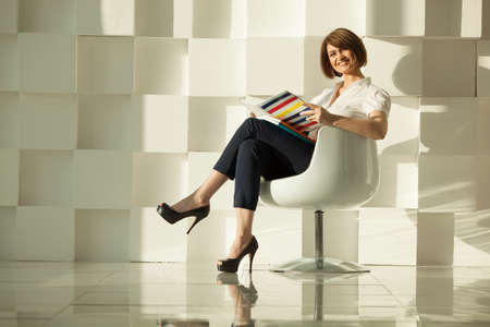 Smiling businesswoman with magazine and crossed legs sitting chair against of modern wall Stock Photo