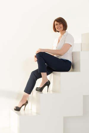 Elegante empresaria mirando a la cámara mientras está sentado en las escaleras contra la pared blanca