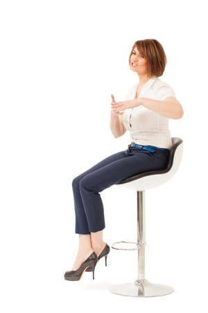 talk show: Attractive adult woman on chair talking and showing something with hands. Isolated, studio shot.