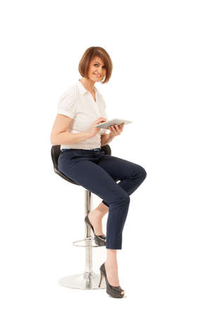 high chair: Elegant businesswoman sitting on chair with pad and looking at camera. Isolated, studio shot.