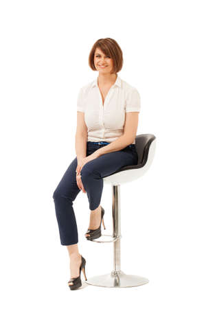 high chair: Attractive adult woman sitting on chair and looking at camera. White background, studio shot. Isolated. Stock Photo