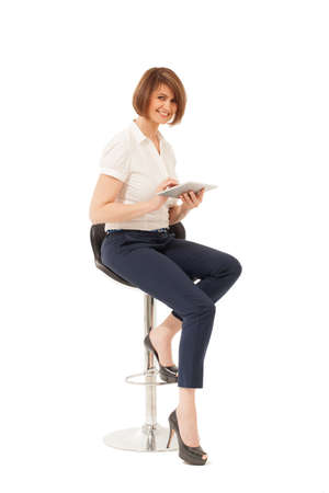 high chair: Portrait of smiling beautiful businesswoman sitting on chair, holding tablet. Isolated, studio shot.