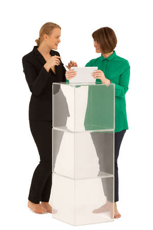 shoeless: Two barefoot women looking to each other while talking near stand made of glass cubes. One of them holding tablet. White background. Isolated