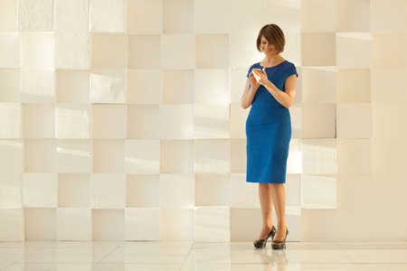 blue wall: Attractive woman in blue dress standing against modern wall while looking at smartphone in her hands
