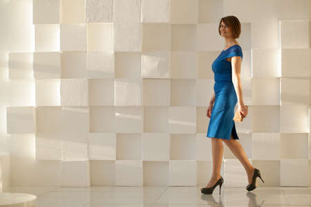 Smiling woman in elegant blue dress walking against modern wall with wallet in hand while looking at camera