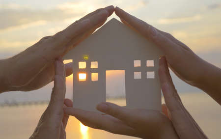house diagram: Group of human palms on all sides of a cut out house diagram with setting sun coming through window over water