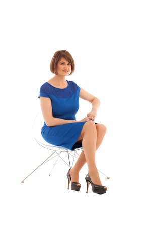 short haired: Short haired woman sitting on transparent chair while looking at camera on white background. Isolated Stock Photo