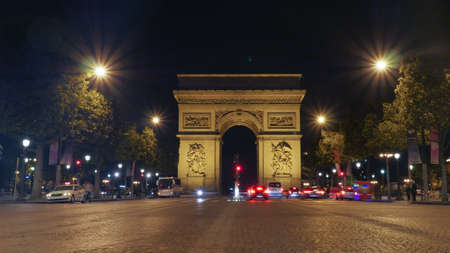 champs elysees: View along the Champs Elysees of the Arc de Triomphe, Paris illuminated at night with vehicular traffic on the street Stock Photo