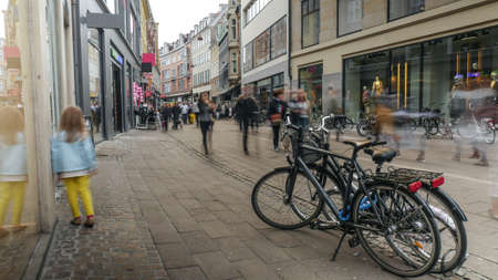 Unidentified child in yellow pants walking along busy street with parked bicycles in Copenhagen Stock Photo