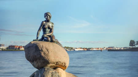 Front view of Little Mermaid statue on large boulders in Denmark with harbor under blue sky in the background