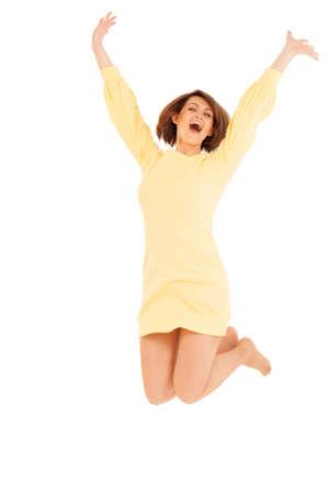 Porträt der glücklich lächelnde Frau im gelben Kleid Springen vor weißem Hintergrund. Isoliert, Studio gedreht.