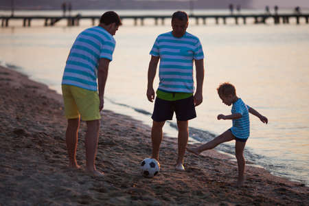 sandy beach: Full Length of Three Generations Playing Soccer on Beach - Grandfather, Father and Son Kicking Football on Sand near Shore at Dusk