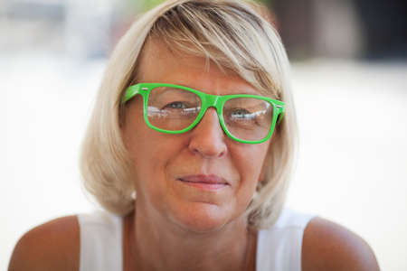 medium length: Relaxed middle-aged woman with medium length blond hair looking at camera while wearing trendy eyeglasses with green plastic frames in summer