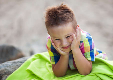 leaning on elbows: Close Up of Young Boy Wearing Colorful Plaid Shirt and Lying on Stomach with Head Resting in Hands on Green Blanket on Beach, Smiling and Looking Down