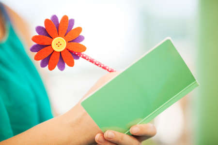 journals: Close Up of Unrecognizable Woman Writing with Pencil Topped with Colorful Flower in Notebook with Plain Green Pastel Colored Cover Stock Photo