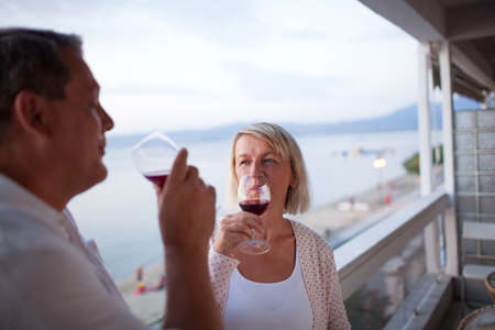 waterfront: Casual Portrait of Mature Couple Drinking Red Wine Together on Balcony of Beachfront Hotel Resort - Man and Woman Toasting Vacation at Dusk Stock Photo