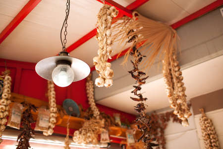 quaint: Low Angle View of Lamp and Dried Garlic and Peppers Hanging from Ceiling Inside Quaint Food Market