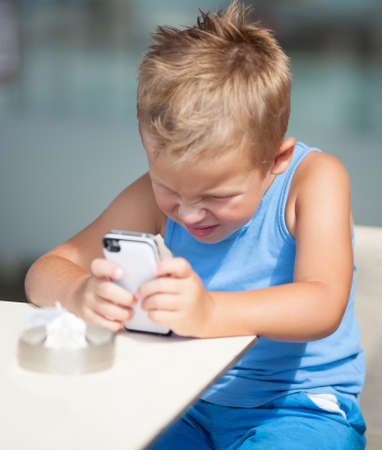 peering: Young boy sitting at a table peering closely at a mobile phone screen with his face screwed up in concentration Stock Photo