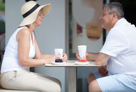 side table: Smiling couple of tourists having breakfast in outdoor cafe while sitting at table and talking Stock Photo