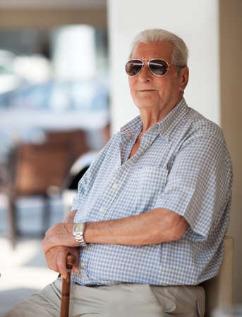 Senior man in sunglasses sitting waiting with his hands resting on his walking stick outside a restaurant or cafeteria looking at the camera with a thoughtful expression