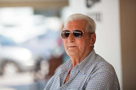 hombre mayor de pelo blanco en camisa a cuadros mirando away.Bokeh