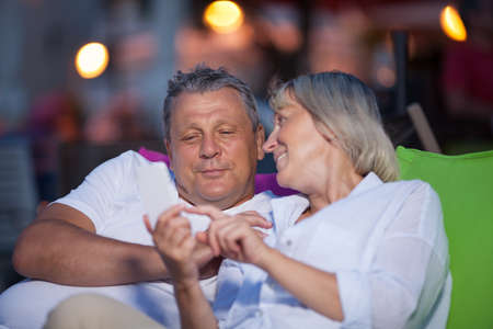 quality time: Loving middle-aged couple having an intimate chat sitting close together smiling and gesturing as they spend quality time together