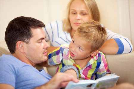 indulgent: Father reading to his intelligent curious young son explaining something to him watched by an indulgent mother