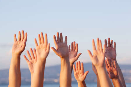 Group of people pulling hands in the air in sunlight Stockfoto