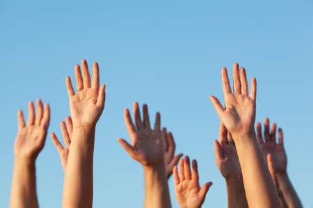 Grupo de gente levantando las manos en el aire contra un cielo azul claro y soleado en una imagen conceptual con espacio de copia