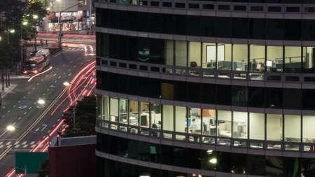 personas trabajando en oficina: Primer plano de los trabajadores en el edificio de oficinas en la carretera con tráfico de coche evening.Exposed Foto de archivo
