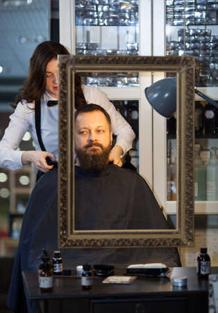 indulging: Middle-aged man having his beard and hair trimmed at an upmarket barber shop by a young woman in a bow-tie