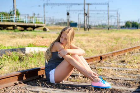 adolescence: Lonely and sad teenager girl sitting on rusty rail track in the countryside. Adolescence problems