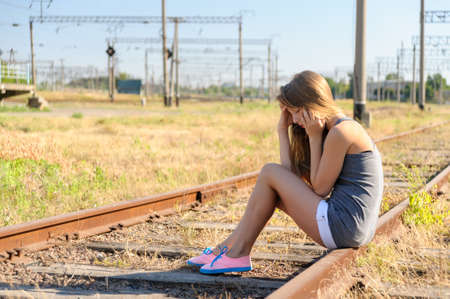 Sad girl teenager sitting on rusty rail track outside the town. Escape to be alone Stock Photo