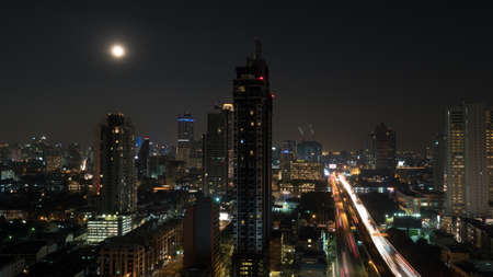 moon  metropolis: Bangkok panorama at night. View to the illuminated high-rise buildings and skyscrapers with transport traffic on highway. Capital of Thailand