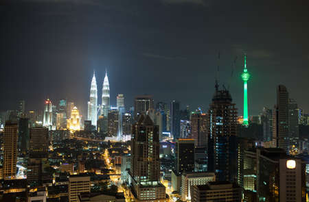 dominating: Panorama of Kuala Lumpur at night. Illuminated buildings and skyscrapers in the capital of Malaysia. Menara KL Tower and Petronas Towers dominating over the city architecture
