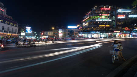 dynamic movement: HANOI, VIETNAM - OCTOBER 27, 2015: Night city with lighted trails of moving transport on the road and buildings with illuminated banners Editorial
