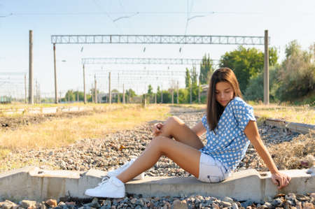 Brunette girl teenager sitting on the concrete of unfinished rail track outside the city Stock Photo