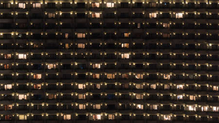 apartment block: Facade of highrise apartment block with balconies. Electric lights in some windows. Housing in Bangkok, Thailand