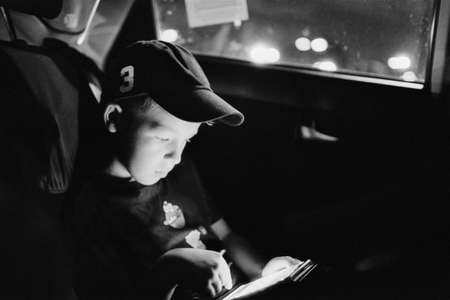 A boy, watching his smartphone, seating in a car at night