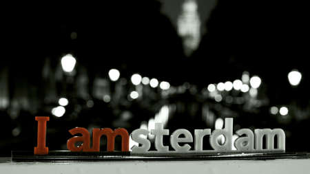 An inscription I amsterdam with a night Amsterdam channel on the background