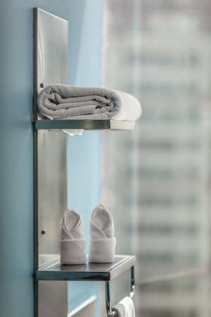 A metallic towel organizer with several towels, arranged on two shelves and a holder