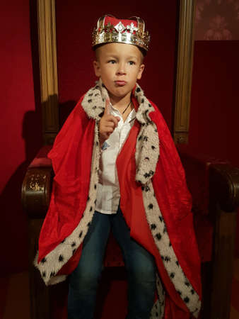 A little boy in a crown and a mantle is ready to rule with his forefinger up