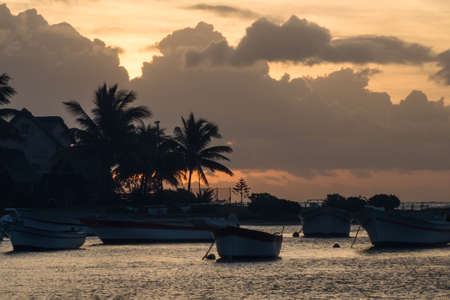 A small bay in Mauritius with several anchored boats at dusk