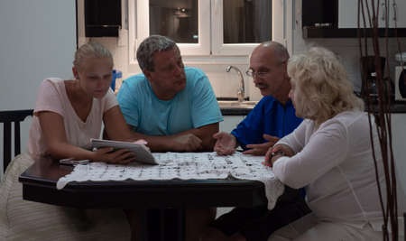 A group of four people of different age, sitting around the kitchen table, talking and looking at a pad Stok Fotoğraf