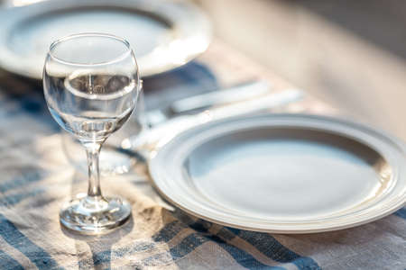 A fragment of a laid table with a tablecloth, a couple of plates, glasses and cutlery Фото со стока