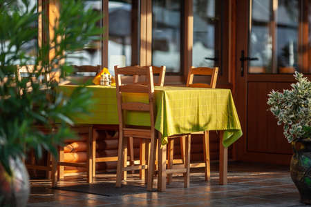 A table on a summer cafe terrace - covered with morning sunlight and a light-green tablecloth