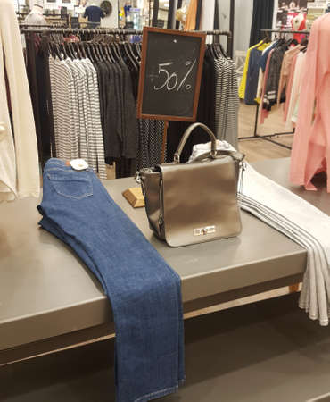 A counter in a clothes store with a couple of jeans, a bag ang a board with 50 procent discount announcement