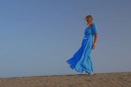 A young woman is standing on the sand against the sky, wind blows over her hair and long sky blue dress Imagens - 121705041